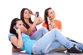Three girls with phones — Stock Photo