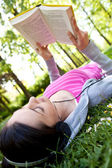 Girl reading a book and listening music in park — Stock Photo