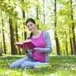 Student enjoying with book in nature — 图库照片