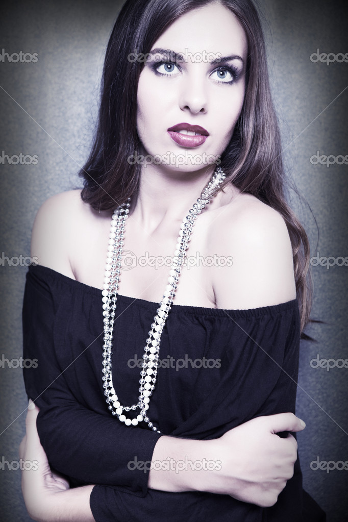 Stunning brunette  posing in fashion dress with pearls — Stock Photo #6117936