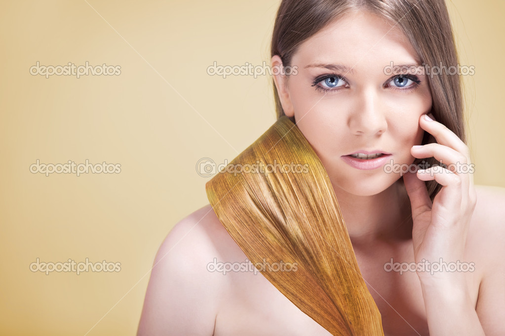 Woman dissatisfied with her skin, holding yellow leaf — Stock Photo #6321210