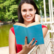 Pretty young girl reading book - Stock Photo