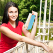 Woman reading book in the park - Stock Photo