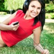 Woman lying on grass listening to music — Stock Photo #6384110