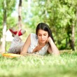 Stock Photo: Student girl reading book in park