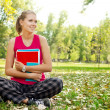 Student in park hugging books - Foto Stock