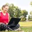 Woman using laptop in park — Stock Photo #6530229