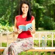 Smiling girl with book on bench — Stock Photo
