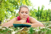 Girl with book in park — Stock Photo