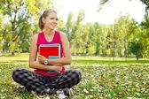 студент в парке, обнимая книги — Стоковое фото