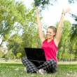 Happy woman with laptop on nature — Stock Photo
