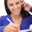 Smiling girl on phone making notes, — Stock Photo