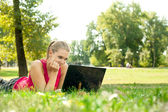 Women using laptop in park — Stock Photo