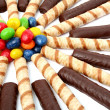 Chocolate sticks with a cream and the multi-coloured sweets isol — Stock Photo