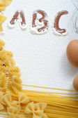 Uncooked macaroni and eggs on wheat flour — Stock Photo
