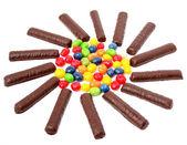 čokoládové tyčinky s krém a izolovaných na pestrobarevných sladkostí květi — Stock fotografie