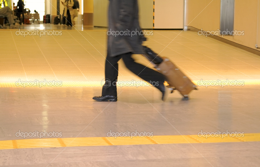 Motion blur image of a traveller carrying suitcase in an airport. — Stock Photo #5389146