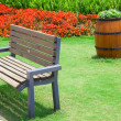 Beautiful summer garden with bench and big decorative wooden flo — Stock Photo