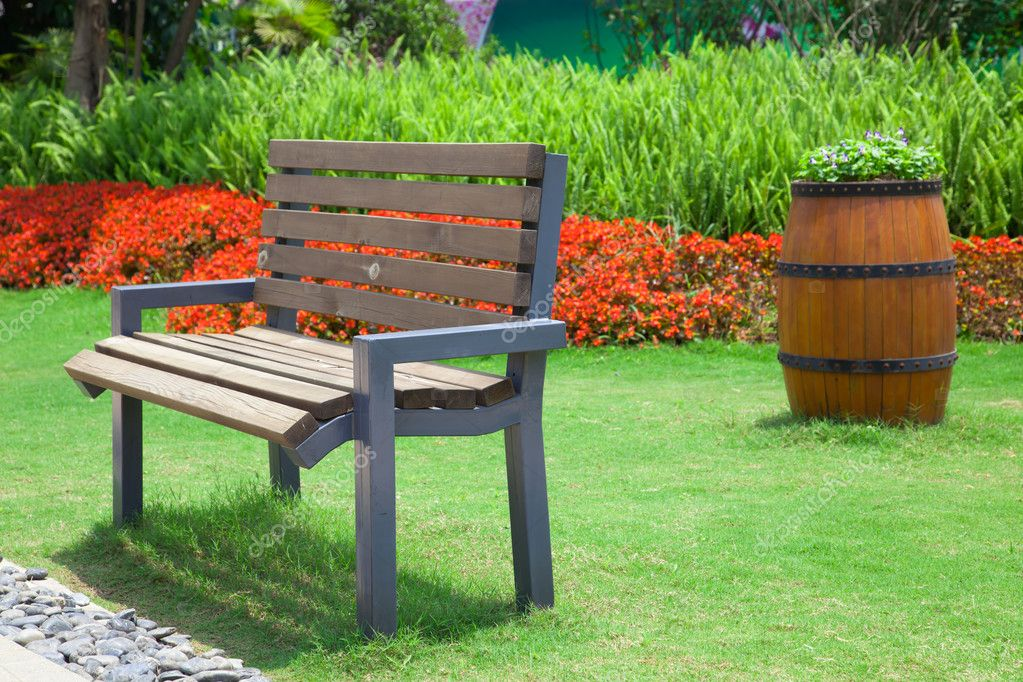 Beautiful summer garden with bench and big decorative for Beautiful wooden benches