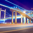 The light trails on the modern suspension bridge background - Stock Photo