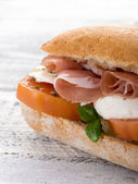 Sandwich with parma ham mozzarella and tomatoes — Stock Photo
