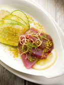 Tuna carpaccio with slice cucumber and grind pistachio — Stock Photo