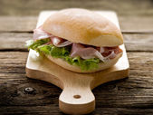 Sandwich with parma ham and green salad — Stock Photo