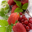 Stock Photo: Strawberries and blackcurrant over wood