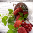 Strawberries and blackcurrant over wood — Stock Photo