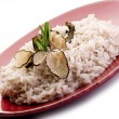 Rice with truffle over red dish — Stock Photo