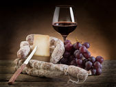 Cheese salami grapes and red wine — Stock Photo