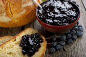 Blueberry jam with bread on wood background — Stock Photo