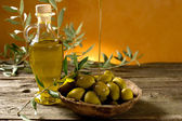 Olive oil on wood background — Stock Photo