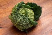 Savoy cabbage on wood background — Stock fotografie