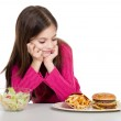 Little girl with healthy and unhealthy food — Stock Photo