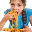 Cute little girl eating spaghetti - Stock Photo