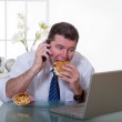Manager eating unhealthy food at work place — Stock Photo #6516863