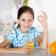 Little girl drinking orange juice — Stock Photo