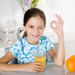 Little girl drinking orange juice — Stock Photo #6555417