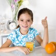 Little girl with orange juice thumbs up — Stock Photo