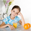 Bored little girl with orange juice — Stock Photo