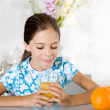 Little girl tongue out looking orange juice — Stock Photo #6555448