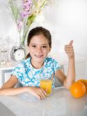 Dziewczynka z soku pomarańczowego kciuki — Zdjęcie stockowe