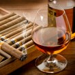 Cuban cigar and bottle of cognac on wood background — Stock Photo