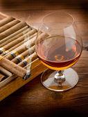 キューバ産の葉巻とコニャックの木製の背景 — ストック写真