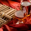Cuban cigar and  liquor  over red satin — Stock Photo