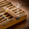 Smoking cuban cigar over box  on wood background — Stock Photo