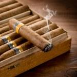 Smoking cuban cigar over box on wood background — Stock Photo