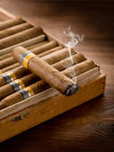 Smoking cuban cigar over box on wood background — ストック写真