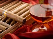 Cuban cigar and liquor over red satin — Stock Photo